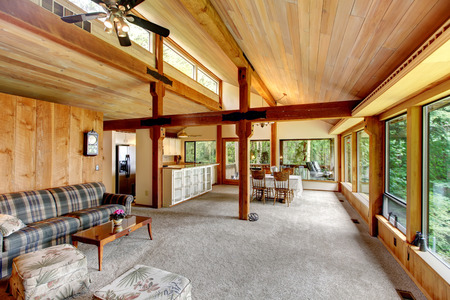 open floor plan: Open floor plan in log cabin house. View of living room and kitchen with dining area Stock Photo