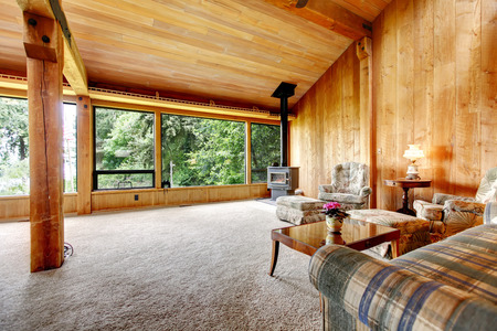 log cabin: Spacious log cabin living room with high vaulted ceiling and carpet floor.  View of antique stove and furniture set