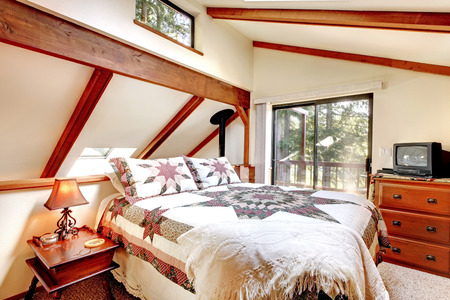 Soft tones bedroom interor with ceiling beams and carpet floor  View of bed with white refreshing bedding and dresser with tv Stock Photo - 29422552