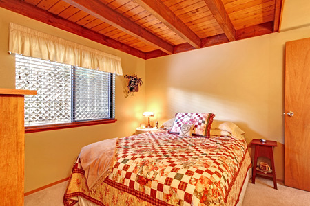 Soft tones bedroom interor with ceiling beams and carpet floor  View of bed with colorful bedding photo