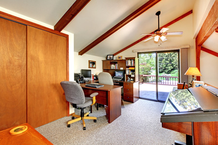 Loft office room with ceiling beams and carpet floor  Furnished with office furniture and piano  View of glass door to walkout deck Archivio Fotografico