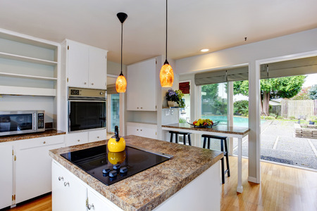 Kitchen room with white appliances, kitchen island and walkout deck to backyard photo