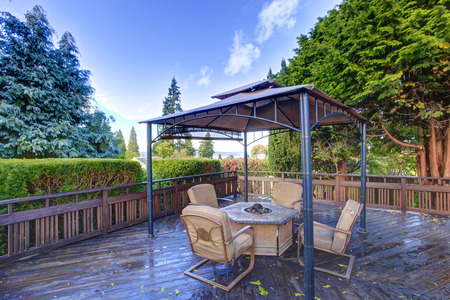 Wooden deck with railings and gazebo with fire pit and chairs