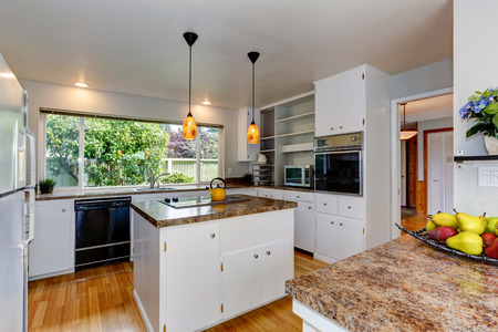 Kitchen room with white appliances, kitchen island and wide window