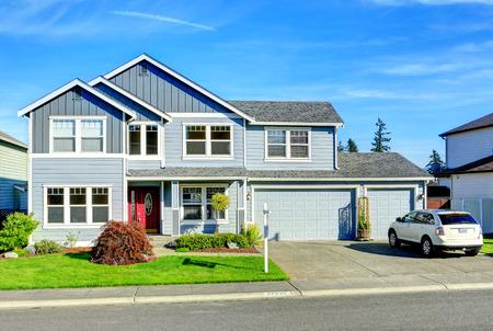 Lichtblauw huis met twee verdiepingen met kolom entree veranda, garage en oprit uitzicht Stockfoto