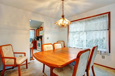 dining table and chairs: Cozy bright dining room with wooden table and comfortable chairs.