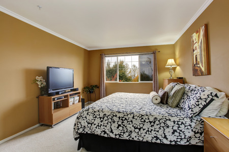 Bedroom in mustard color with light ivory carpet floor. View of bed in white and black, wooden cabinets photo
