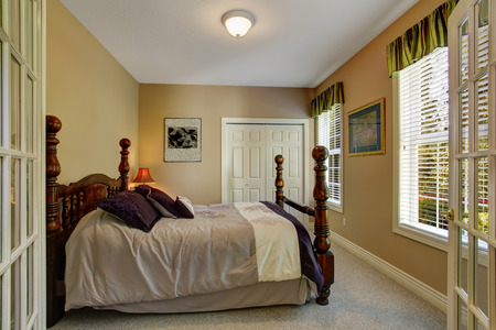 french doors: Beige bedroom with closet and carved wood bed with high poles