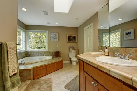 bathroom wall: Spacious bathroom with tile wall trim and corner bath tub. View of bathroom vanity cabinet Stock Photo