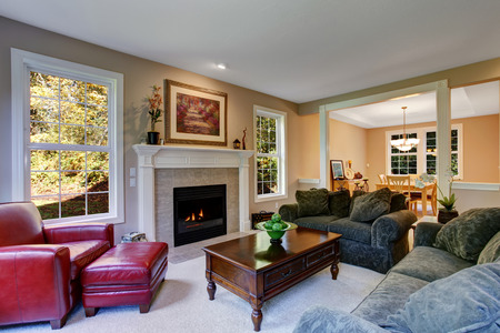 Cozy living room with fireplace, dark green sofas and red leather armchair. View of antique coffee table with drawers