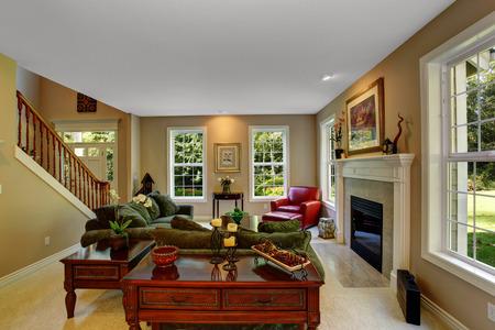 벽난로가있는 아늑한 거실, 짙은 녹색 소파와 빨간 가죽 안락의 자입니다. drawerse 골동품 커피 테이블보기