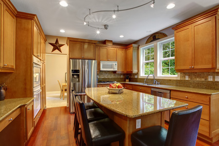 kitchen island: View of elegant kitchen area with kitchen island and black leather chairs