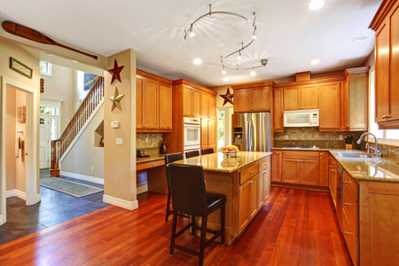 open floor plan: Open floor plan. View of elegant kitchen area with kitchen island. View of entrance hallway with stairs