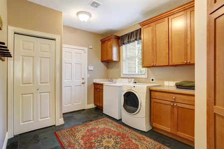 Spacious laundry room with tile floor and rug. Wooden cabinets with white appliannces photo