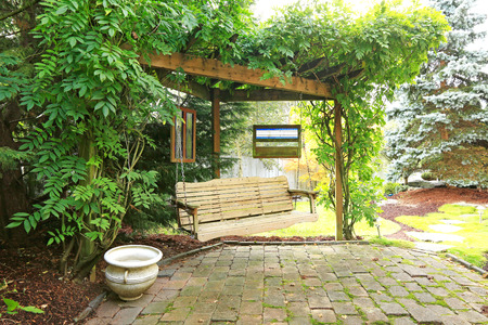 Summer backyard garden with rest area  View of wooden hangin bench and brich floor