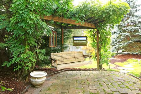 brich: Summer backyard garden with rest area  View of wooden hangin bench and brich floor