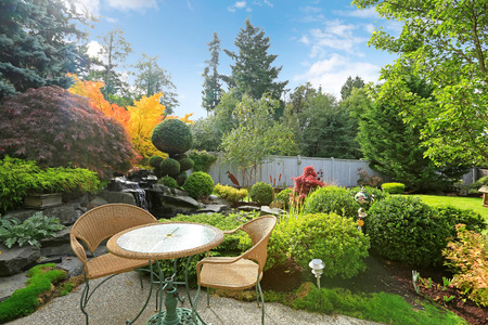 northwest: Backyard area with table and wicker chairs surrounded by tropical garden with waterfall Stock Photo