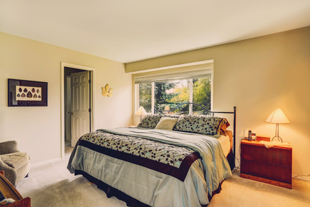 Light tones bedroom with window and iron frame bed with olive bedding Stock Photo - 29688514