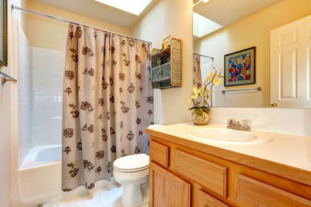 bathroom design: Soft colors bathroom with honey tone bathroom vanity cabinet, large mirror. View of bath rub with curtains Stock Photo