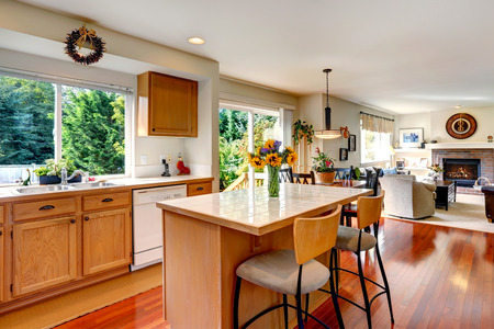 Kitchen area with honey color cabinets, white appliances and kitchen island with fresh flowers. View of living room Stock Photo - 29688521