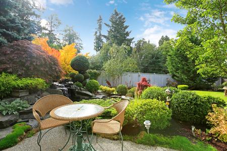 Achtertuin met tafel en rieten stoelen omgeven door tropische tuin met waterval Stockfoto