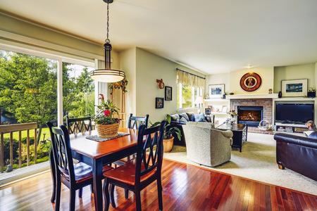 open floor plan: House interior. Open floor plan. View of living room with dining table set and open door to walkout deck