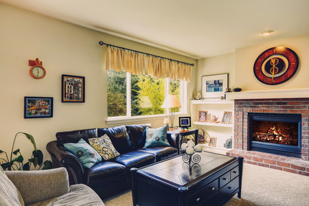 Living room interior with brick background fireplace, leather furniture set and black coffee table with drawers photo