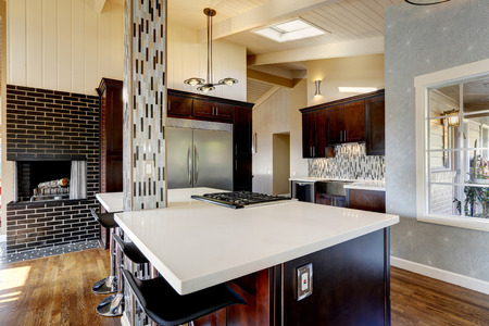 counter top: Modern kitchen with dark brown cabinets, steel appliances and kitchen island with bar stools