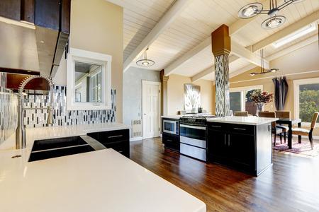 appliances: Modern kitchen with dark brown cabinets, steel appliances and kitchen island with bar stools