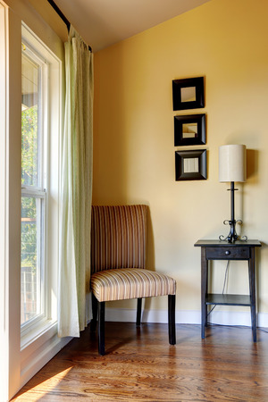 furnished: Simple room corner furnished with striped chair, small table and lamp.