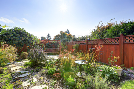 fenced: Fenced backyard with small garden and wooden hanging bench
