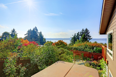 garden bench: Backyard garden with hanging bench and lake view from walkout deck Stock Photo