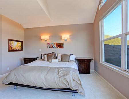 nightstands: Soft brown master bedroom with queen size bed and nightstands.