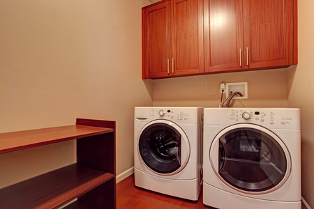 dryer  estate: Small laundry room with brown cabinets, shelf and white modern appliances