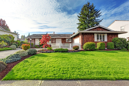 white trim: One story house with brick wall trim and clapboard siding. View of green front yard with white wooden fence