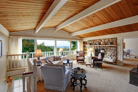 vaulted ceiling: Old fashion living room with vaulted wood plank ceiling, walkout deck and rocky fireplace. View of antique furniture