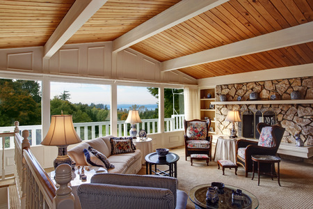 living room window: Old fashion living room with vaulted wood plank ceiling, walkout deck and rocky fireplace. View of antique furniture