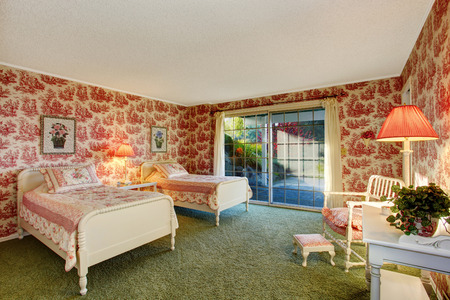 old furniture: Bright old fashion bedroom with walkout deck, red wallpapers and green soft carpet floor. Furnished with antique beds, chair and table