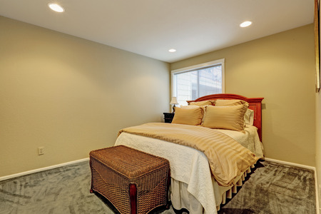 Small bedroom with dark green carpet floor, one bed and wicker ottoman photo
