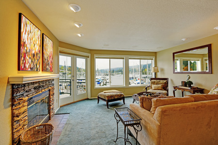 Living room with walkout deck and water front view. Furnished with antique sofa and chair photo