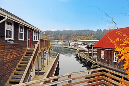 Old wooden houses with water front view. View of private boats photo