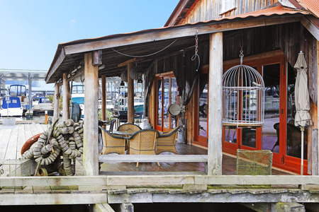 gig harbor: Wooden old building with wicker table set. View of boats behind it. Gig Harbor. Stock Photo