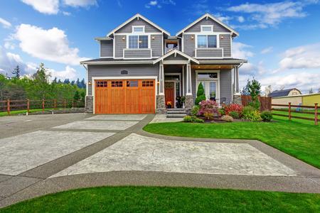 Huis exterieur. Groot huis met kolom veranda, garage en oprit uitzicht
