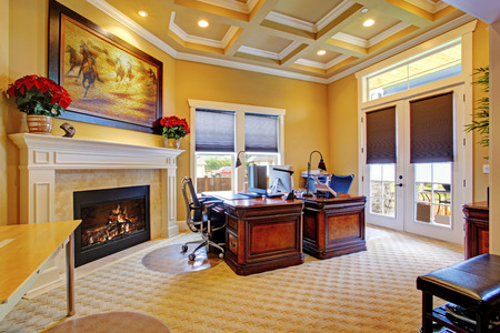Luxury office room interior with coffered ceiling, fireplace and wood carved desks