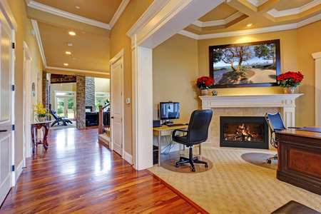 home office interior: Luxury house interior. Office room with fireplace and hallway with shiny hardwood floor