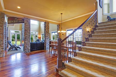 casa de lujo con techos altos columnas de piedra y piso de madera vista