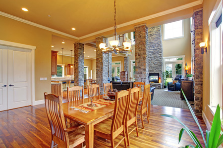 ceiling: Luxury house with high ceiling and brick columns. View of dining room with long table