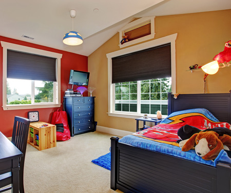 bedroom: Colorful kids room with beige and red walls. Furnished with single bed and desk