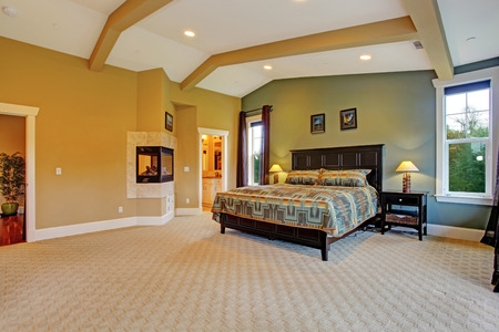 master bedroom: Spacious master bedroom with high coffered ceiling, beige carpet floor and fireplace built in the wall