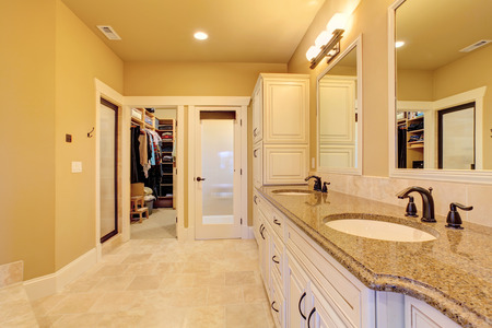 Soft ivory bathroom interior with tile floor and walk-in closet photo